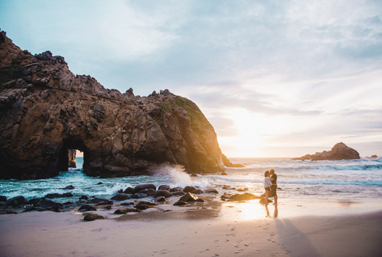Engaged travel couple adventure to Pfeiffer Beach in Big Sur, California for photos at sunset next to the famous rock archway