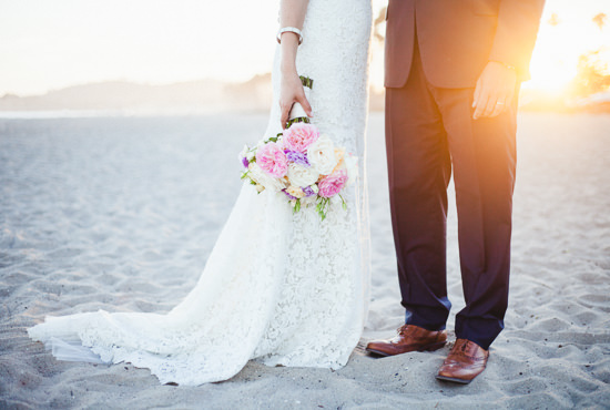 Bride and groom with wedding bouquet at sunset on the beach in Santa Barbara, California
