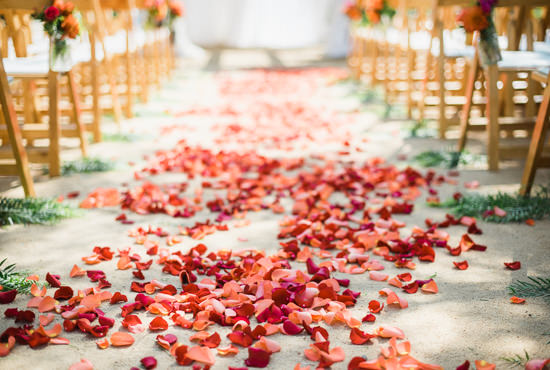 Red flower petals cover the aisle of a beautiful and colorful wedding ceremony at the Santa Barbara Historical Museum