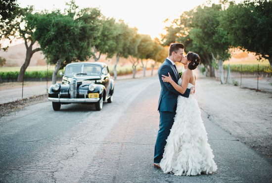 Bride and groom at sunset with a classic car after their Santa Ynez wedding at Firestone Vineyards